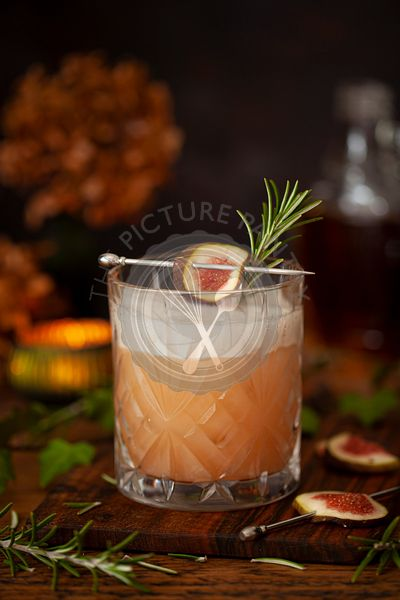 A tumbler of Fig bourbon sour cocktail with egg white foam, fig and rosemary garnishes