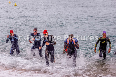 Ironman Barcelona men coming out of the sea after their swim
