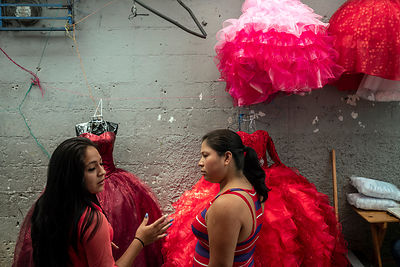 Two girls discuss red dresses at a stall in Guatemala City
