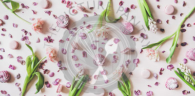 Flat-lay of macaron cookies, marshmallows and flowers over pink background