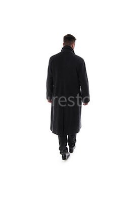 A Figurestock image of a mystery man walking away, in a long black winter coat – shot from eye level.
