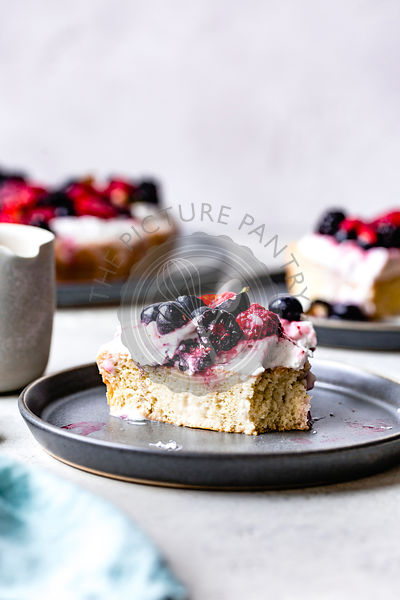 Berry tres leches cake on ceramic plates.