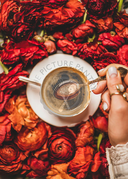 Womans hand holding spoon of espresso coffee over red flowers