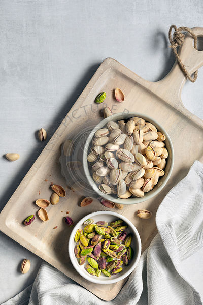 Roasted pistachio nuts in shells with a bowl of kernals.