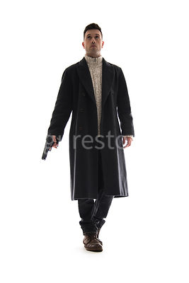 A Figurestock image of a man in a long black winter coat, holding a gun, walking towards camera – shot from low level.