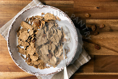 Breakfast bowl of wheat bran flakes and dried sultanas with milk.