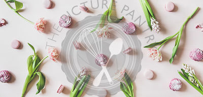 Macaron cookies, marshmallows and flowers over pink background, top view
