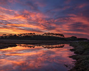 Twilight clouds with intense dawn colour and perfect reflections on the River Otter at Budleigh Salterton, Devon, UK