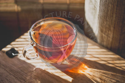 A cup of hot tea on sunny day near a window