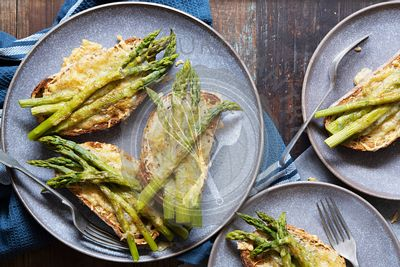 Servings of grilled cheese and asparagus on sourdough bread.