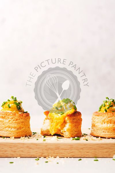 Three Vol-au-Vent filled with cauliflower and saffron sauce, lined on a wooden cutting board and sprinkled with cheese and ch...