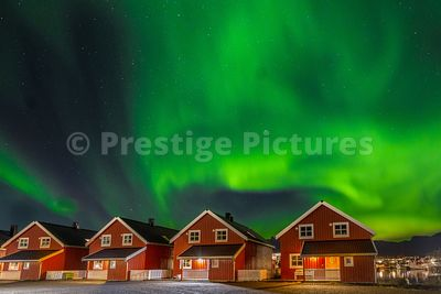 Northern Lights in the sky over wooden red houses by  the harbour in Svolvær, Norway