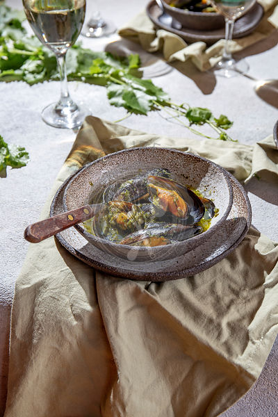 Mediterranean style dinner. Close up of table with Mussels in green sauce and white wine.