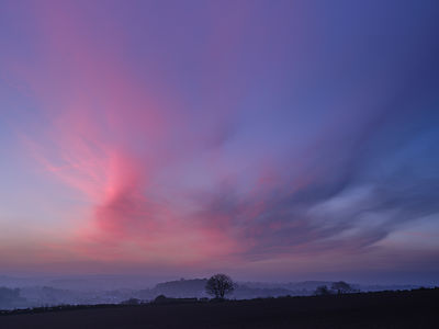 Clouds with twilight glow and a misty Otter Valley, near Otterton, Devon, UK