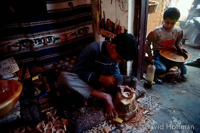 Boys making wooden bowls for sale to tourists in a small workshop, Essouaria, Morocco. 1991