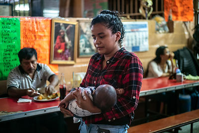 A woman cradles her baby at a cafe