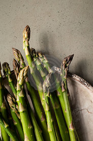 Fresh, raw asparagus on a rustic, crackled plate, on a concrete background.