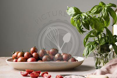 Straight on view of cherry tomatoes in an oval platter with a sprigs of basil and a bottle of wine.
