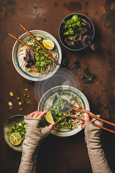 Vietnamese soup Pho Ga and womans hands with chopsticks, flat-lay