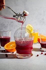 Fresh squeezed pomegranate juice being poured into orange juice