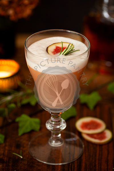 A Bourbon sour cocktail flavoured with fig and rosemary and topped with egg white foam.
