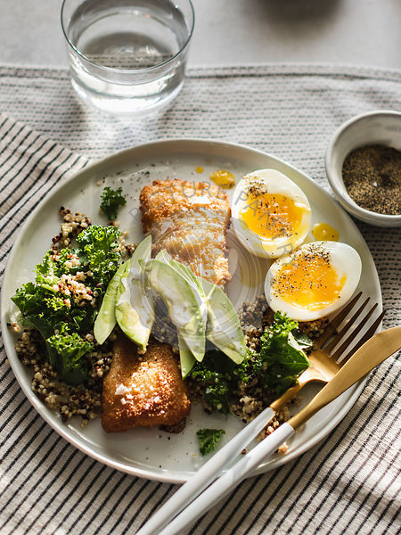 Baked tilapia with quinoa, kale and avocado with soft boiled eggs on the side