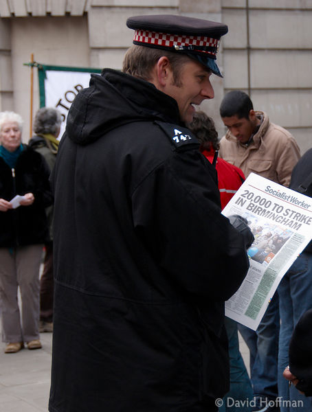Policeman reads a copy of Socialist Worker during a Media Workers Against The War demonstration