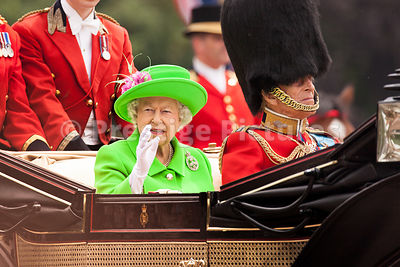 The Queen waves to teh Crowd as she and Prince Philip return to Buckingham Palace after Trooping the Colour