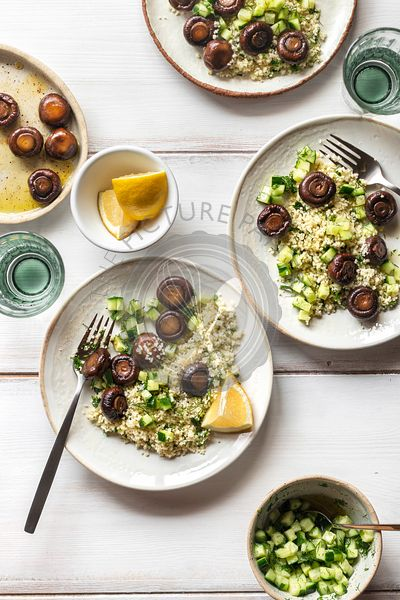 Couscous salad with roasted mushrooms and cucumber on white background