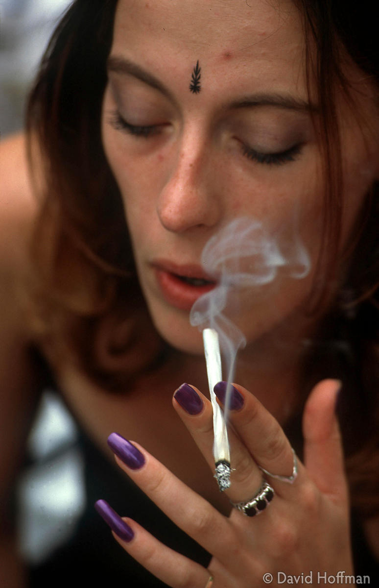 4.211-566 Young woman smoking cannabis joint in Hyde Park. Model released.