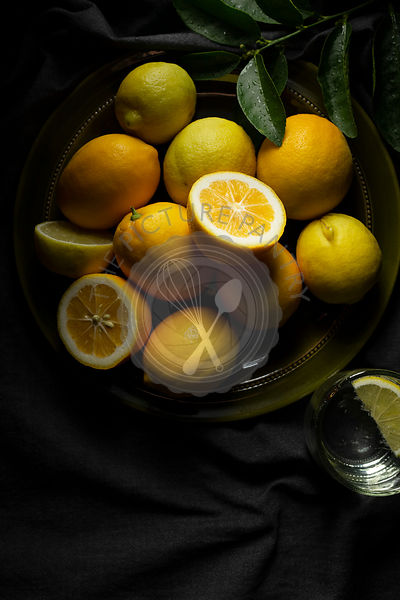 An olive green plate of home grown lemons on a dark grey linen tablecloth, with a glass of water.