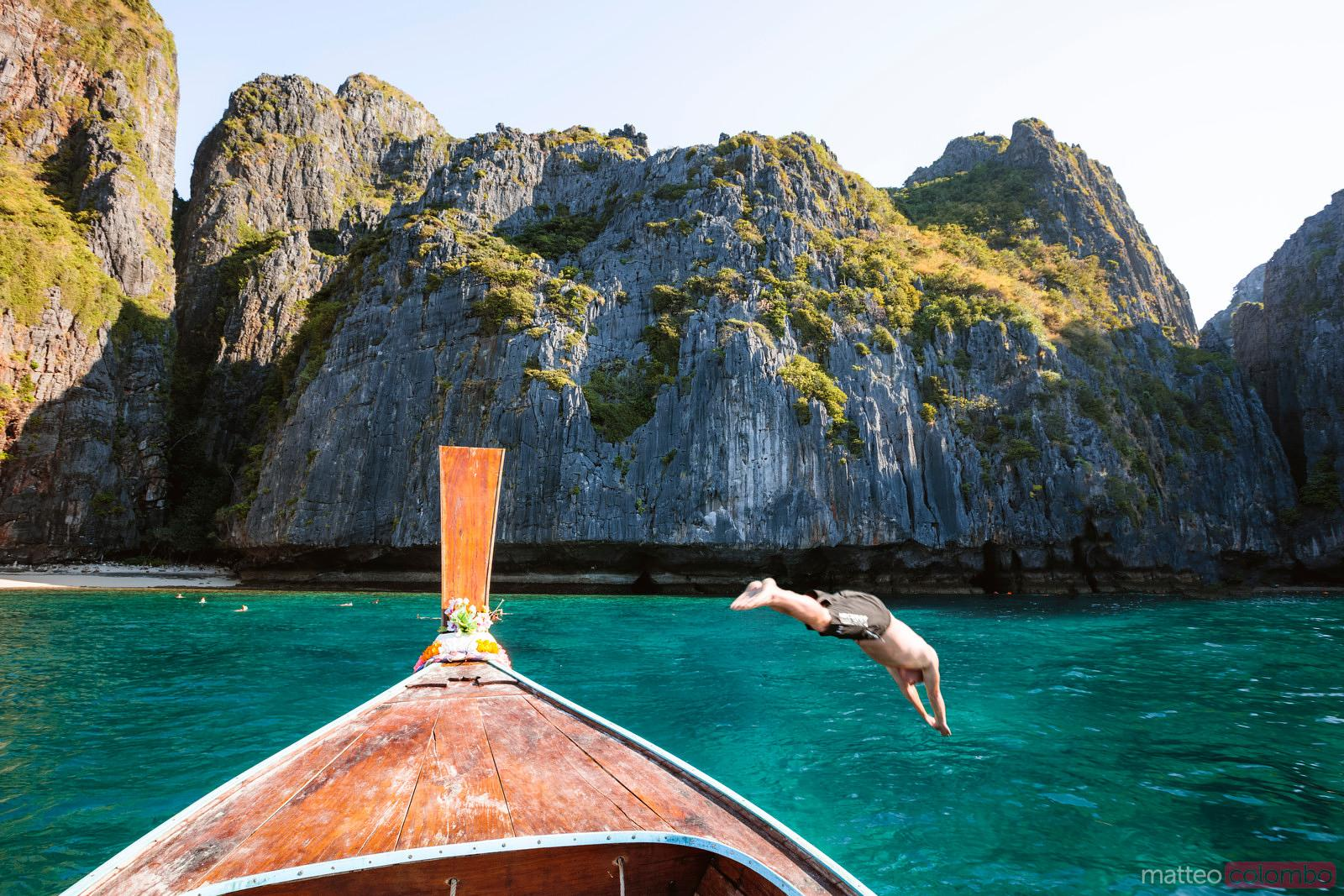 Man diving from boat prow, Phi Phi island, Thailand