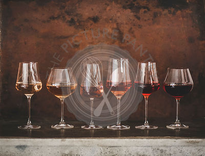Shades of Rose wine in glasses, rusty background, copy space