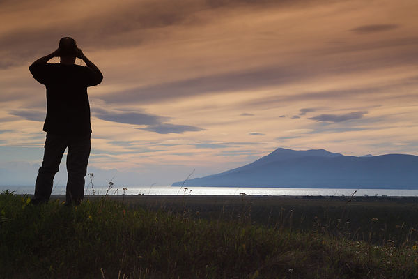 Silhouette of a man with binoculars against a pastel orange sky, viewing over Lake Fagano on  Tierra del Fuego.