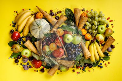 Flat-lay of fruits and berries and ice cream cones on yellow background.