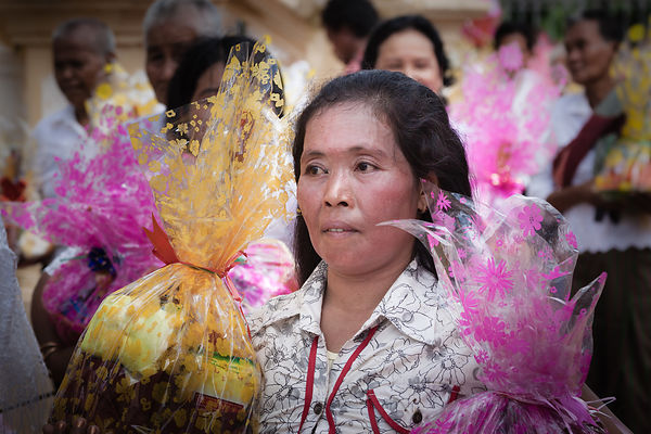 To celebrate the Festival of the Ancestors, a woman is bringing gifts to offer in the temple of Wat Dhum Rey Sor in Battamban...
