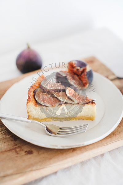 Slice of homemade fig cheesecake with figs on wooden board