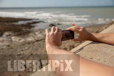 GAY MAN TAKING PHOTOGRAPHS ON THE BEACH