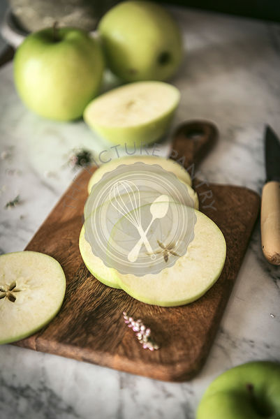 Fresh ripe green apple, sliced oon a work surface in a kitchen