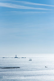 Sailing boat passing Longships Lighthouse of Land's End, Cornwall - BP6745