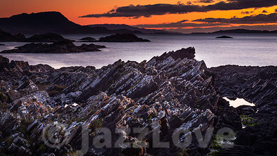 Colourful sunset on rocky beach, on west  coast of Scotland.