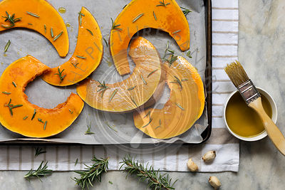 Preparation of sliced pumpkin for roasting on a baking tray.
