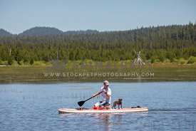 Man and small dog on stand up paddle board on lake with teepee in background