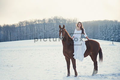 A woman in a white dress, riding a horse in the snow.