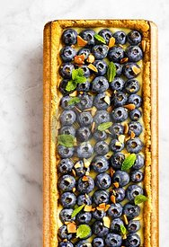 Overhead shot of a rectangular blueberry tart with mint and almonds on a marble countertop.