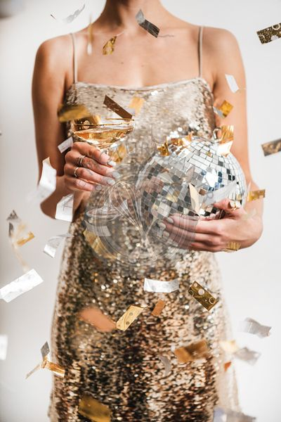 Woman holding glass of champagne and discoball for New year