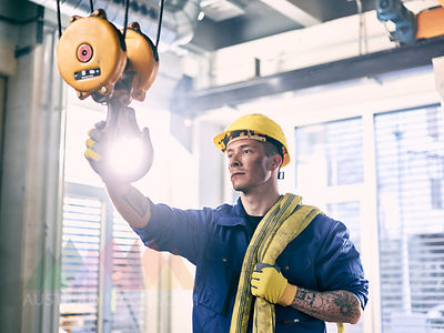Industrial worker fixing hoist sling on indoor crane