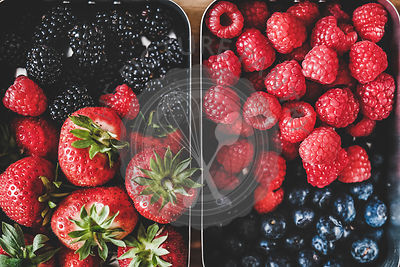 Fresh seasonal berries in metal lunchboxes, close-up, top view