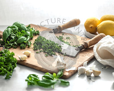 A knife with two handles resting in a pile of minced, green herbs on a wood cutting board, surrounded by lemons, cloves of ga...