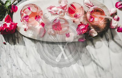 Rose lemonade with ice and fresh rose petals, copy space
